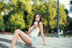 Happy beautiful girl sitting on stairs in park and drinking ice coffee Royalty Free Stock Photo