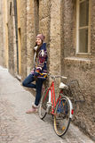 Happy beautiful girl is standing next to a bicycle in small stre Stock Photos
