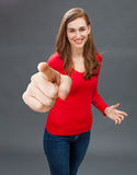 Happy beautiful girl for successful emphasis or cheerful accusation. Happy beautiful girl standing, aiming at someone with a big index forward for concept of Royalty Free Stock Photos