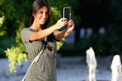 Happy beautiful girl taking a selfie photo in park. Royalty Free Stock Photos