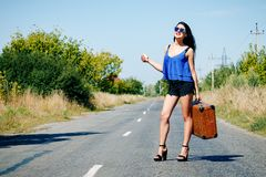 Happy beautiful girl traveler with a suitcase on the road, hitch royalty free stock photography
