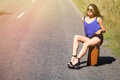 Happy beautiful girl traveler with a suitcase on the road, hitch stock photography