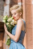 happy beautiful girl in trendy blue dress with bouquet royalty free stock image