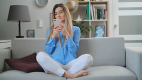 Happy beautiful girl using digital mobile device browsing the internet, staying connected at home enjoying modern stock video