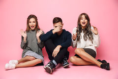 Happy beautiful girls and sad guy sitting over pink background. Stock Photography