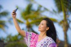 Happy beautiful and gorgeous Asian Chinese woman in glamour dress taking self portrait selfie photo with mobile phone at holidays stock image