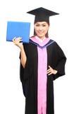 Beautiful graduation girl holding her diploma. Happy beautiful graduation girl holding her diploma Royalty Free Stock Photo