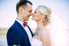 Happy and beautiful groom and bride tender kiss at spring outdoo Stock Images