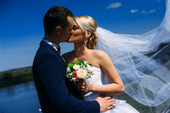 Happy and beautiful groom and bride tender kiss at spring outdoo Stock Photo