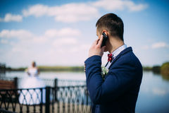 Happy and beautiful groom is speaking by mobile phone  at spring Stock Photography