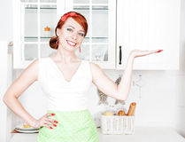 Happy beautiful housewife presenting Stock Photos