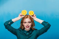 Happy beautiful joyful red-haired girl with makeup in a green blouse on a blue background stock photo