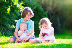 Happy beautiful kids in the garden. Three happy kids, brothers and sister, laughing teenager boy, little baby and a funny curly girl playing together with royalty free stock photo