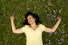 Happy beautiful latin woman lying on the green grass sleeping and meditating Stock Photo