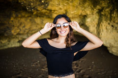 Happy beautiful latin woman  wearing sunglasses smile near on rocks beach on summer vocation time Stock Photography