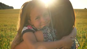 Happy beautiful little daughter hugging mother and smiling at camera, wheat or rye field during sunset in background
