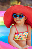 Happy beautiful little girl in a bathing suit and a hat swims in. The pool Royalty Free Stock Photo