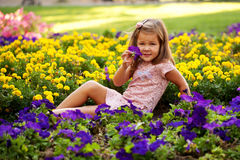 Happy beautiful little girl with flowers. Stock Photos
