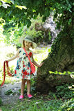 Happy beautiful little girl kid child in white dress and red neckerchief on forest background Royalty Free Stock Images