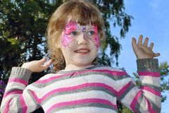 Happy beautiful little girl with pictured purple butterfly. On face outdoor stock photography