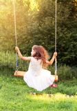 Happy beautiful little girl sitting on seesaw at summer day, bac Royalty Free Stock Photos