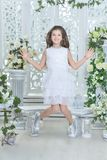 Happy little girl in white dress jumping royalty free stock image