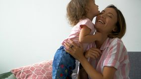 Happy beautiful loving family young mother and daughter laughing sitting on the couch, monkeying and fool around. Smiling mom with child having fun enjoy stock video