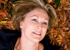Happy, beautiful, mature woman in fall leaves. Happy, beautiful, mature woman lying fall leaves stock photography