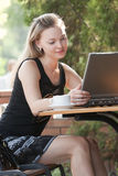 Happy beautiful model in cafe with laptop Royalty Free Stock Image