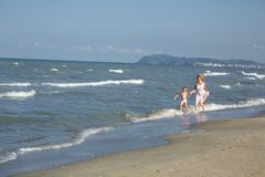 Happy beautiful mom and child running in water along the sea beach Royalty Free Stock Image