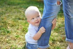 Happy beautiful mother and baby daughter or son. Enjoying in the summer park royalty free stock photo