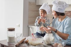 Happy beautiful mother and child preparing dough. At kitchen stock photos