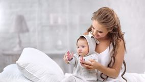 Happy beautiful mother and cute baby having fun playing clapping hand together enjoying morning stock video footage