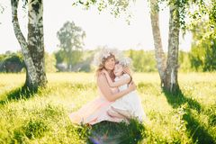 Happy beautiful mother with a daughter of Caucasian appearance hugging in the meadow Royalty Free Stock Photos