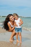 Happy beautiful mother and daughter enjoying beach time Royalty Free Stock Photo