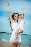 Happy beautiful mother and daughter enjoying beach time Royalty Free Stock Photos