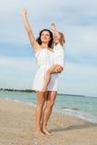 Happy beautiful mother and daughter enjoying beach time Stock Photos