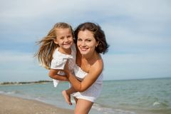 Happy beautiful mother and daughter enjoying beach time Royalty Free Stock Images