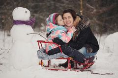 Beautiful mother with daughter in winter park Royalty Free Stock Image