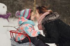 Beautiful mother with daughter in winter park Royalty Free Stock Photo
