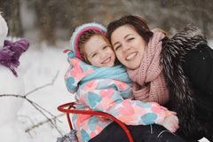 Beautiful mother with daughter in winter park Stock Photos