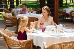 Happy beautiful mother having lunch with younger daughter stock photo