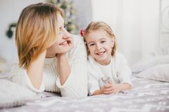 Happy beautiful mother and her little daughter posing near Christmas tree in a holiday interior Royalty Free Stock Images