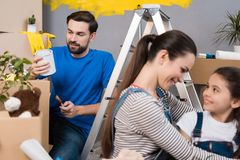 Happy beautiful mother hugs little daughter while father chooses paint to paint wall. Repair in house for sale. Home repair royalty free stock images