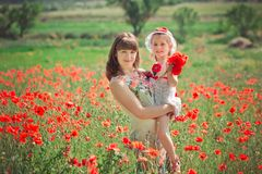 Happy beautiful mother lady posing with her cute little daughter in lovely scene of family summer life on meadow of daisy poppy f stockbild