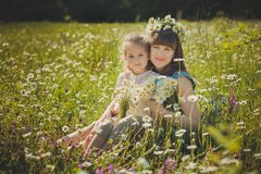 Happy beautiful mother lady posing with her cute little daughter in lovely scene of family summer life on meadow of daisy poppy f stockfoto
