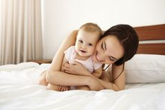 Happy beautiful mother in sleepwear lying on bed with her baby daughter embracing smiling. Copy space Royalty Free Stock Images