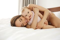 Happy beautiful mother in sleepwear lying on bed with her baby daughter embracing smiling. Copy space Stock Image