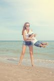 Happy beautiful mother and son enjoying beach time Stock Image