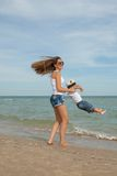 Happy beautiful mother and son enjoying beach time Stock Photography